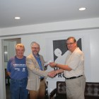 Lion Dave Mair (L) and Lion Dennis Simpson (R) presenting a cheque to a representitive from Harvest Project